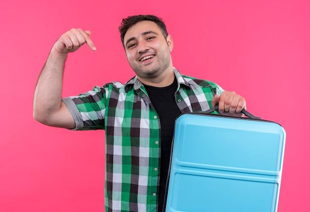 ピンクの壁の上に立っている幸せそうな顔で笑ってそれに指で指しているスーツケースを保持しているチェックシャツの若い旅行者