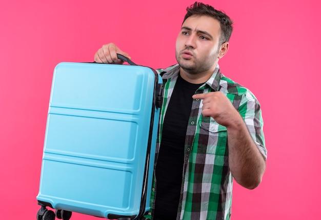 ピンクの壁の上に立って混乱しているように見える人差し指でスーツケースを指しているチェックシャツを着た若い旅行者の男