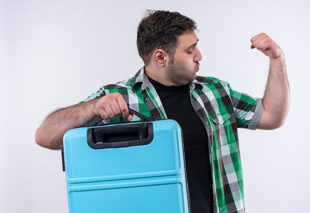 真面目な顔で拳を上げ、上腕二頭筋、白い壁の上に立っている勝者の概念を示すスーツケースを保持しているチェックシャツの若い旅行者