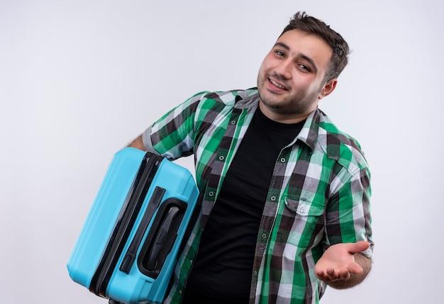 白い壁の上に立って幸せな顔を上げる腕と元気に笑ってスーツケースを保持しているチェックシャツの若い旅行者の男