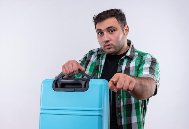 Молодой путешественник в клетчатой рубашке держит чемодан с выражением страха, указывая указательным пальцем, стоит над белой стеной