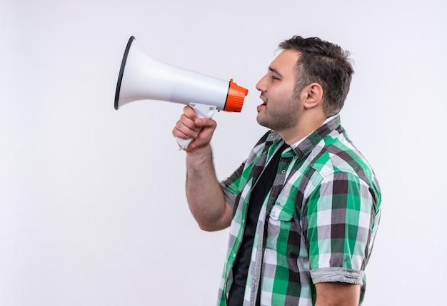 Молодой путешественник в клетчатой рубашке кричит в мегафон, стоя над белой стеной