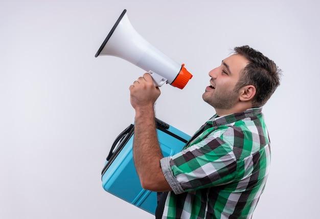 Молодой путешественник в клетчатой рубашке стоит с чемоданом и кричит в мегафон над белой стеной