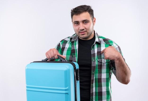 白い壁を越えて自分自身を指している幸せな顔で笑顔のスーツケースと立っているチェックシャツの若い旅行者の男
