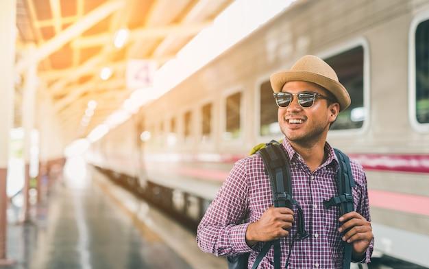 Young traveler man at platform train station. traveling concept.