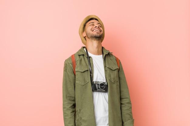 若い旅行者の男はリラックスして幸せな笑い、首を伸ばして歯を見せて