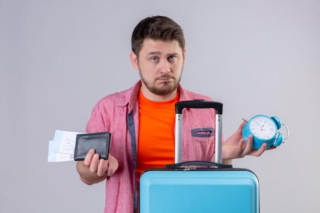Молодой путешественник, стоящий с чемоданом, держит авиабилеты и будильник, недовольно смотрит в камеру на белом фоне