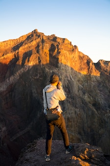 Young traveler man taking a photo on the top of mount