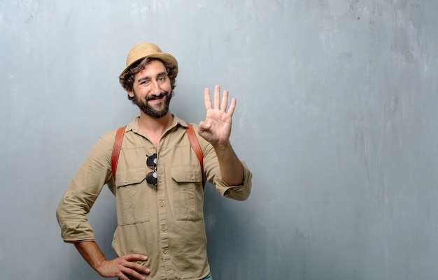 Young traveler man or tourist smiling, counting number four with fingers.