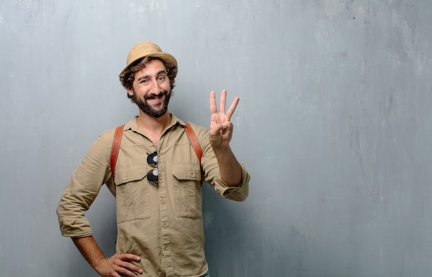 Young traveler man or tourist smiling , counting number three with fingers.