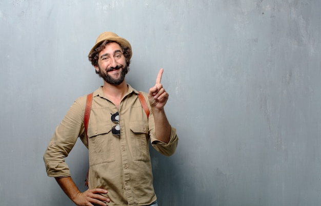 Young traveler man or tourist smiling and looking satisfied and happy, number one