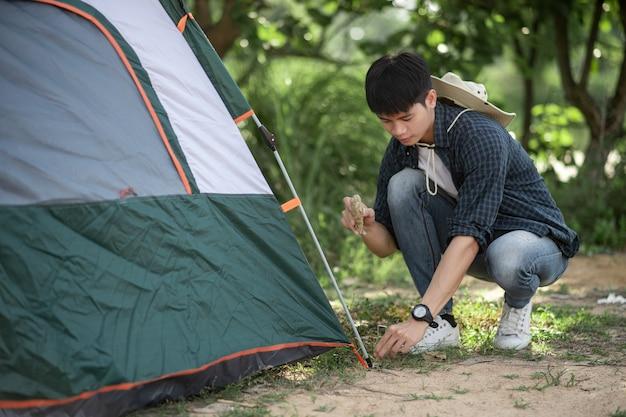 若い旅行者の男性は、夏休みのキャンプ旅行中に森のテントペグに石を打つために使用します
