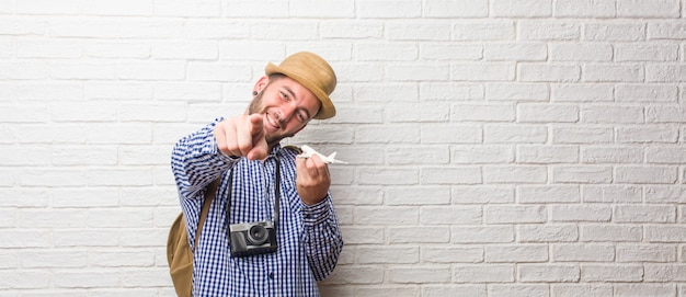 Young traveler man wearing backpack and a vintage camera shouting, laughing and making fun of another, concept of mockery and uncontrol. holding a airplane model.