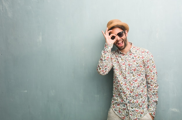 Young traveler man wearing a colorful shirt cheerful and confident doing ok gesture