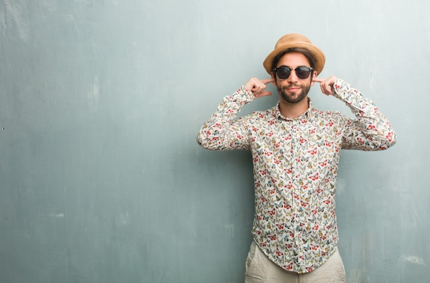 Young traveler man wearing a colorful shirt covering ears with hands