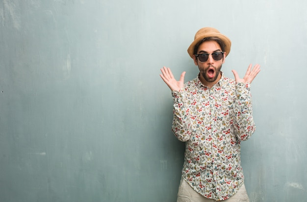 Young traveler man wearing a colorful shirt crazy and desperate, screaming out of control