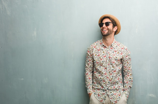 Young traveler man wearing a colorful shirt laughing and having fun