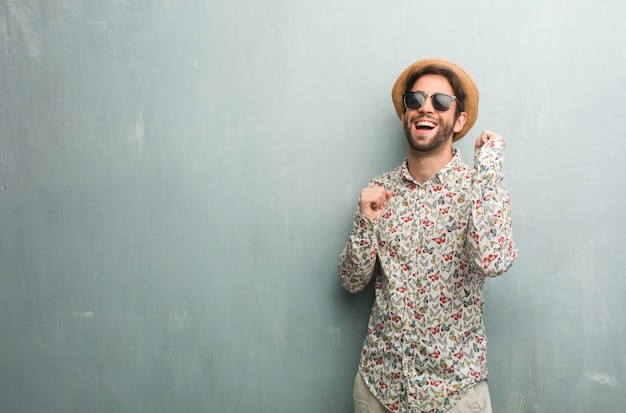 Young traveler man wearing a colorful shirt listening to music, dancing and having fun