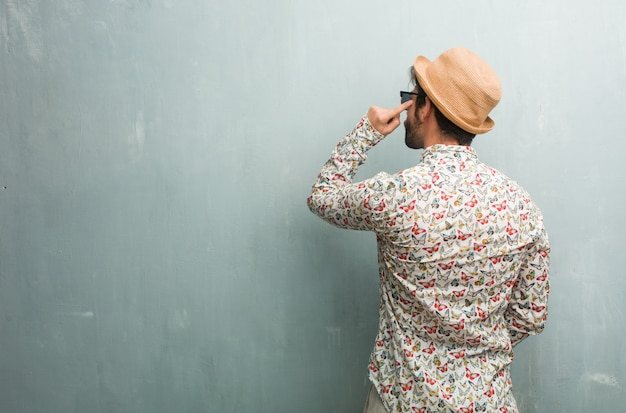 Young traveler man wearing a colorful shirt showing back, posing and waiting, looking back