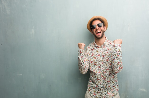Young traveler man wearing a colorful shirt very happy and excited, raising arms