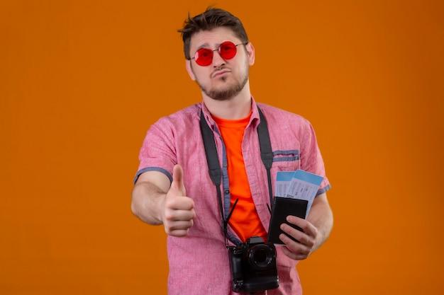 Молодой путешественник в солнцезащитных очках с камерой, держащей авиабилеты, смотрит в камеру с грустным выражением лица и показывает палец вверх, стоя над оранжевым backgroun