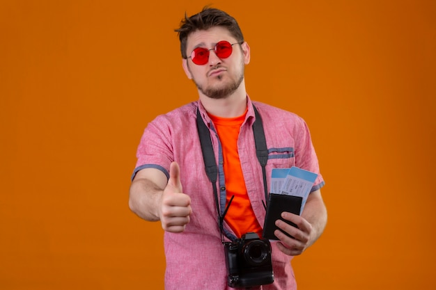 Young traveler man wearing sunglasses with camera holding air tickets looking at camera with sad expression on face showing thumbs up standing over orange backgroun