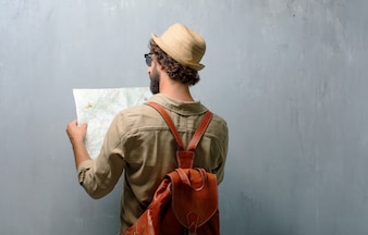 Young traveler man with a map and leather bag