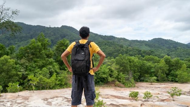 バックパックが立っている若い旅行者の男は、プーケットタイの風景風景山頂に対してリラックスします。