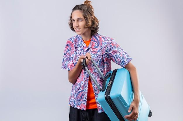 白い背景の上に立って旅行する準備ができて幸せそうな顔で自信を持って笑顔を探している青いスーツケースを持つ若い旅行者男