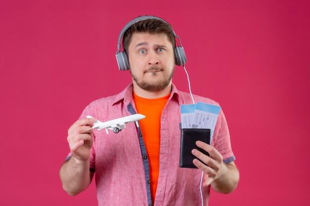 Молодой путешественник с наушниками, держащий игрушечный самолет и авиабилеты, радостный и счастливый, глядя в камеру, смущенный и обеспокоенный, стоя на розовом фоне
