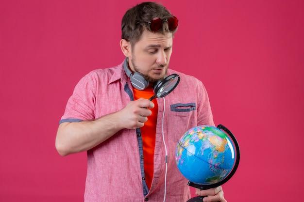 ピンクの背景の上に立って虫眼鏡を通してグローブを見てヘッドフォンで若い旅行者男