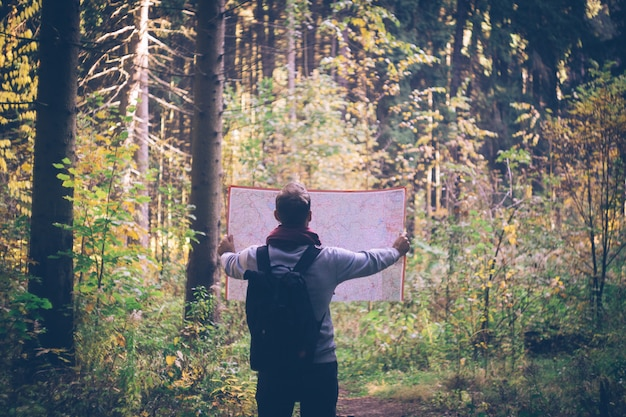 Young traveler man with map, backpack at autumn green forest in sunny day.