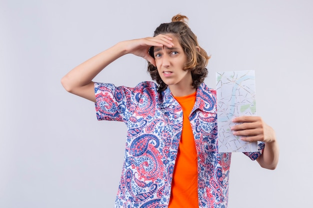 Молодой путешественник с картой смотрит вдаль с рукой, чтобы посмотреть что-то стоящее на белом фоне
