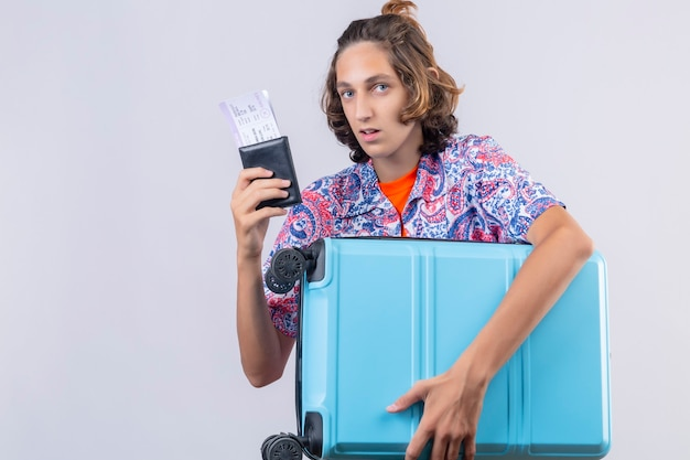 Young traveler man with suitcase holding air tickets looking confused standing over white background