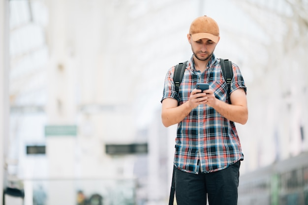 Young traveler on railroad station using phone in train station