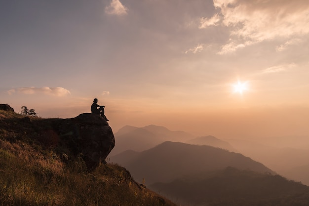 Young traveler relaxing and looking beautiful landscape on top of mountain, adventure travel lifestyle concept