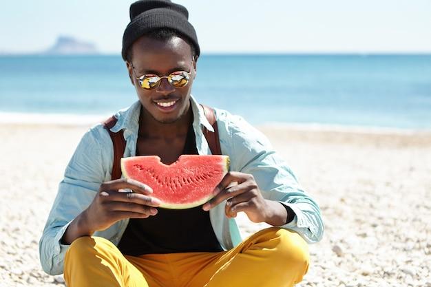 穏やかな紺碧の海と青い空を背景に小石のビーチに座っている若い旅行者