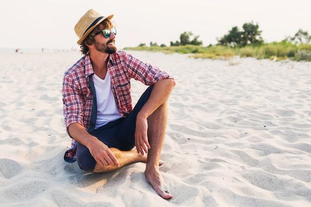 Giovane viaggiatore seduto sulla sabbia bianca