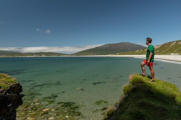 Young traveler standing on cliff admiring keel beach in achill island ireland