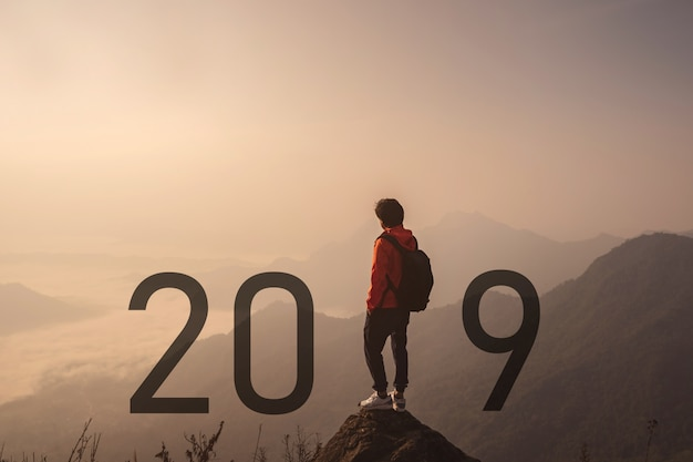 Young traveler standing and looking at beautiful landscape on top of mountain