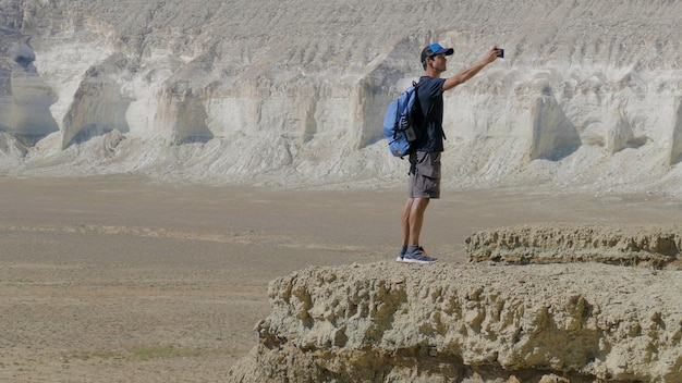 A young traveler stands on the edge of a cliff and makes a selfie