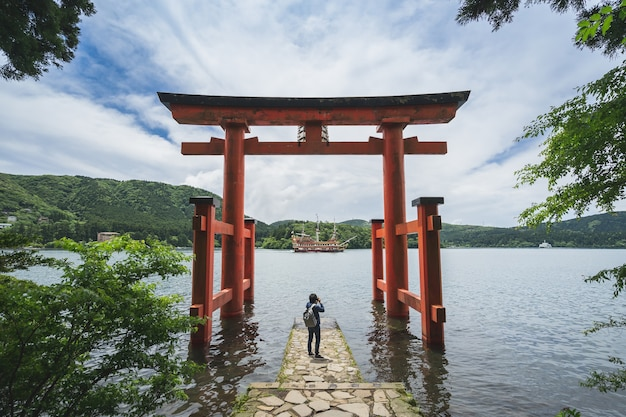 芦ノ湖、日本の箱根神社の赤い鳥居にある若い旅行者の写真
