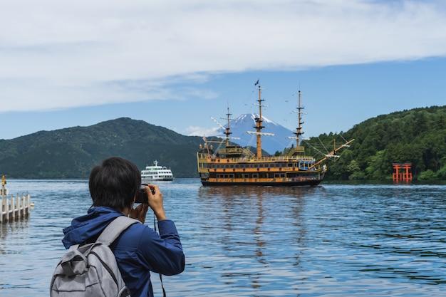 芦ノ湖の箱根神社と富士山の写真を撮っている若者