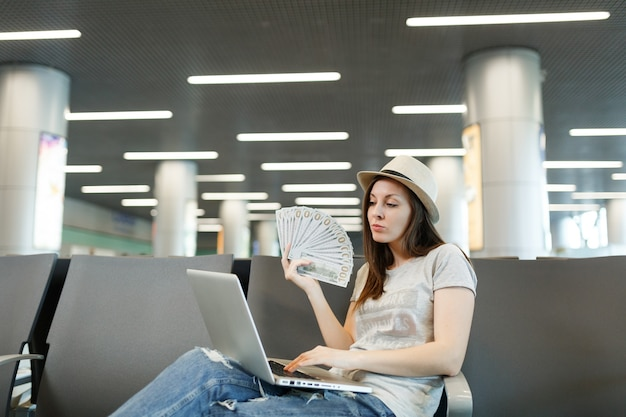 Young traveler tourist woman in hat working on laptop, holding bundle of dollars, cash money while waiting in lobby hall at airport