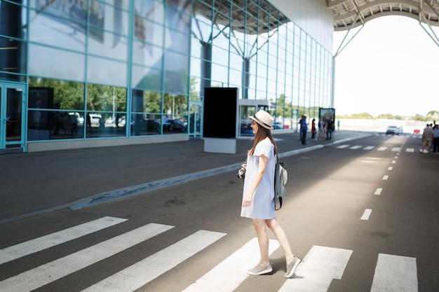 Молодой путешественник турист женщина в шляпе с рюкзаком ретро старинный фотоаппарат на пешеходном переходе в международном аэропорту