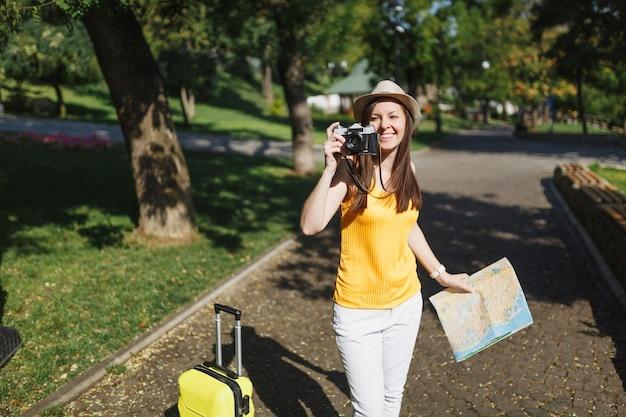 Молодой путешественник туристическая женщина в шляпе с чемоданом, карта города фотографирует на ретро старинный фотоаппарат в городе на открытом воздухе. девушка едет за границу, чтобы поехать на выходные. туризм путешествие образ жизни.