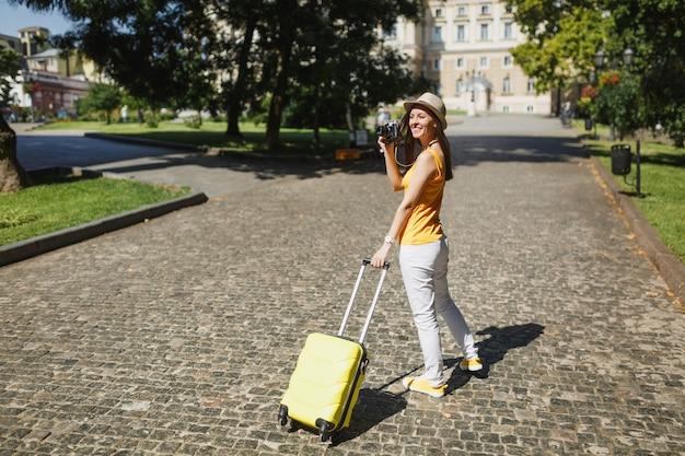Молодой путешественник турист женщина в желтой одежде с чемоданом фотографирует на ретро старинный фотоаппарат, идущий в город на открытом воздухе. девушка выезжает за границу на выходные. туризм путешествие образ жизни.