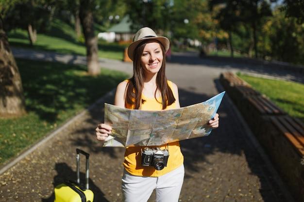 노란색 여름 캐주얼 모자를 쓴 젊은 여행자 관광 여성, 야외 도시 지도를 들고 여행 가방을 들고 있습니다. 주말 휴가를 여행하기 위해 해외로 여행하는 소녀. 관광 여행 라이프 스타일 개념입니다.