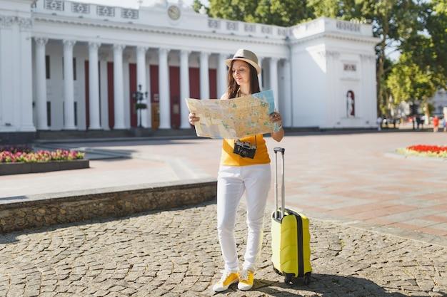 黄色の夏のカジュアルな服を着た若い旅行者の観光客の女性、屋外の都市の都市地図検索ルートを探しているスーツケースの帽子。週末の休暇で海外旅行する女の子。観光の旅のライフスタイル。