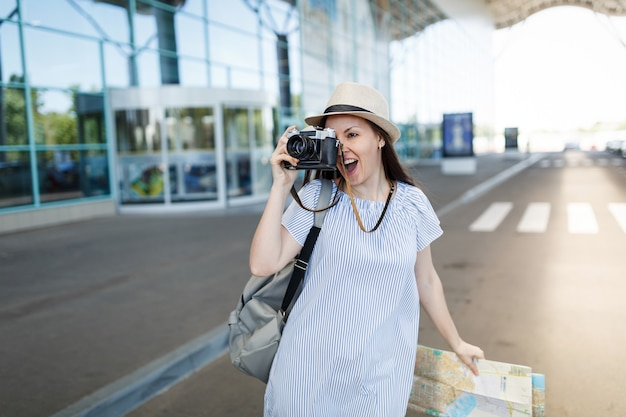 Young traveler tourist woman with backpack holding retro vintage photo camera, paper map at international airport